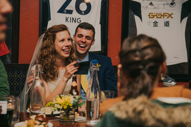 A bride and groom laugh during toasts at a Red Lion Pub wedding