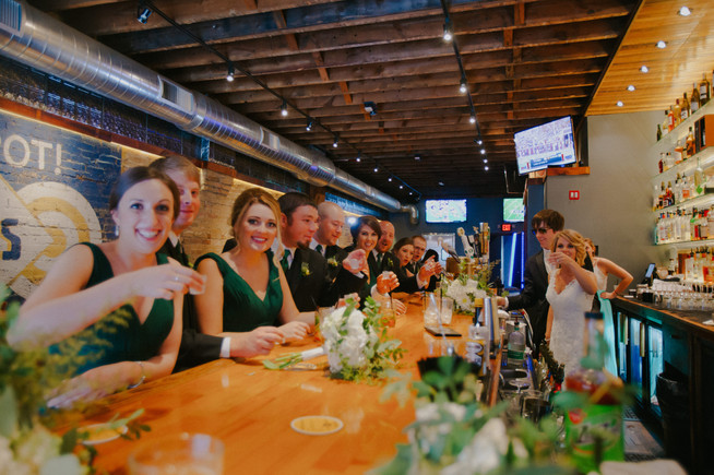 A wedding party takes shots at a bar