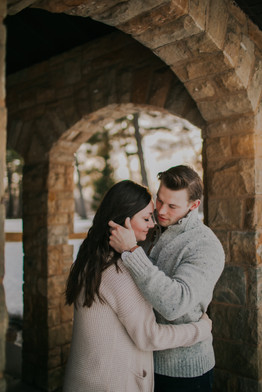 A man tucks a woman's hair behind her ear in Central Wisconsin engagement photos