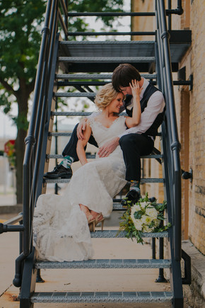 A bride and groom sit on a staircase in in Oshkosh