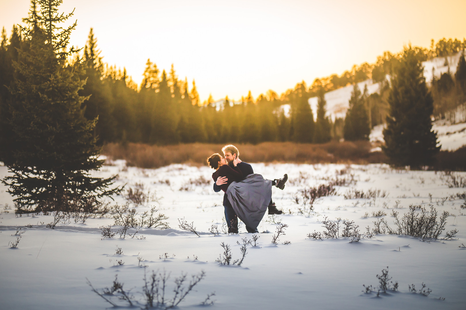 A man holds a woman in his arms in a snowy field at a Horsethief Falls Trail engagement session in Divide Colorado