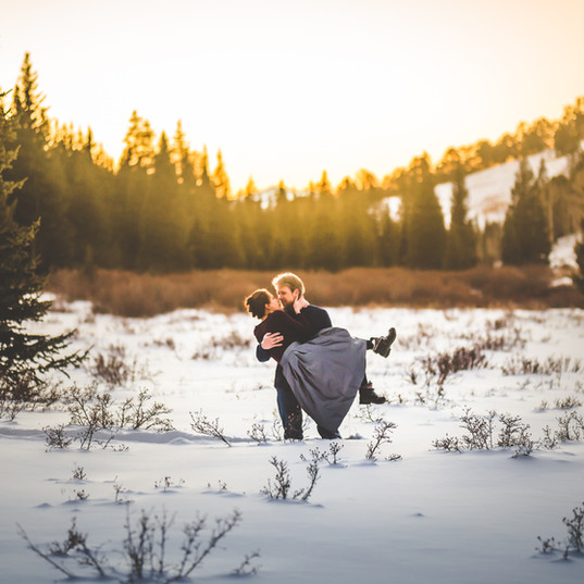 A man holds a woman in his arms in the middle of a snowy field in Colorado