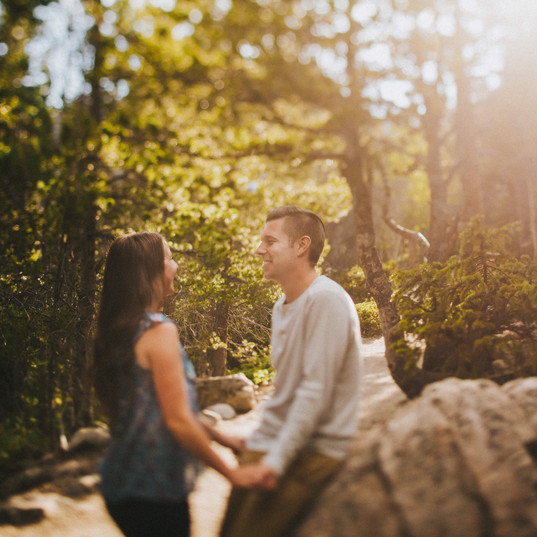 A woman and man hold hands at a Rocky Mountain National Park engagement