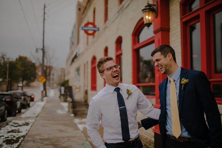 Two men laugh together in front of the Red Lion Pub