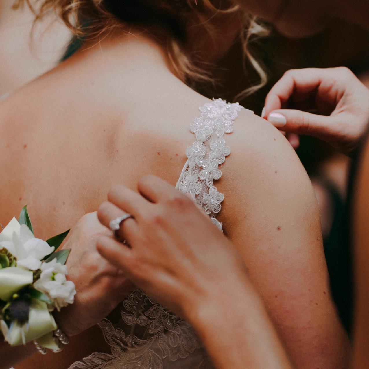 Women adjust the lace strap on a bride's dress