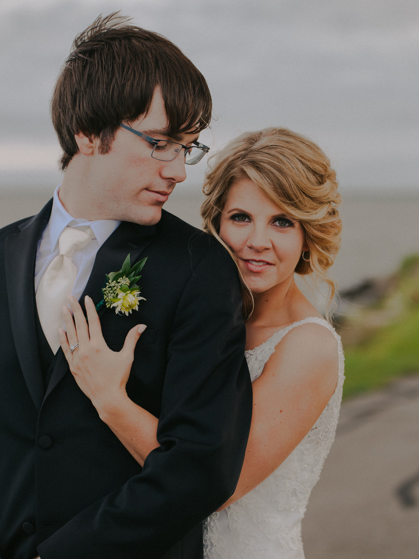 A closeup of a groom and bride in a waterfront wedding