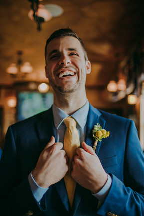 A groom smiles while straightening his suit coat
