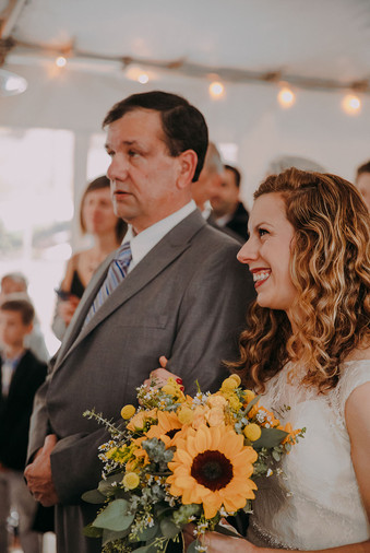 A bride holds onto her father's arm as he gives her away at a Milwaukee wedding ceremony