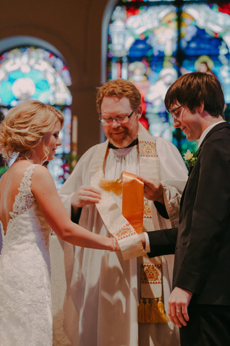 A priest ties a sash around a bride and grooms hand during a wedding