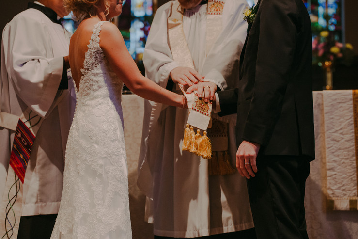 A priest gives a blessing during a hand tying wedding ceremony Wisconsin