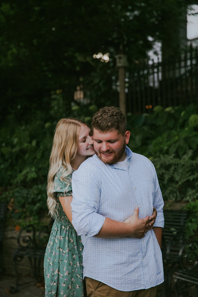 A woman whispers into a man's ear during Wisconsin engagement photos