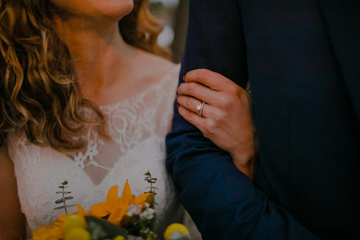 A close up of a bride's wedding and engagement rings as she holds onto her grooms arm in a Milwaukee, Wisconsin wedding