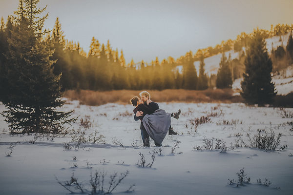 A man and woman kiss in a snowy field during winter engagment session in Estes Park, CO