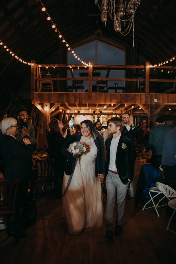 A bride and groom are welcomes in to their barn reception at Emily's Ten Oaks Ranch in Madison Wisconsin