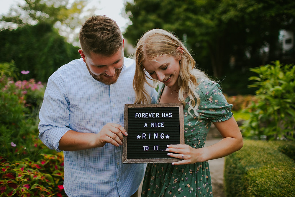 A man and woman smile down at a changeable letter sign that is announcing their engagement