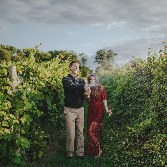 A man and woman laugh and spray a champagne bottle in  vineyards at a Villa Bellezza wedding