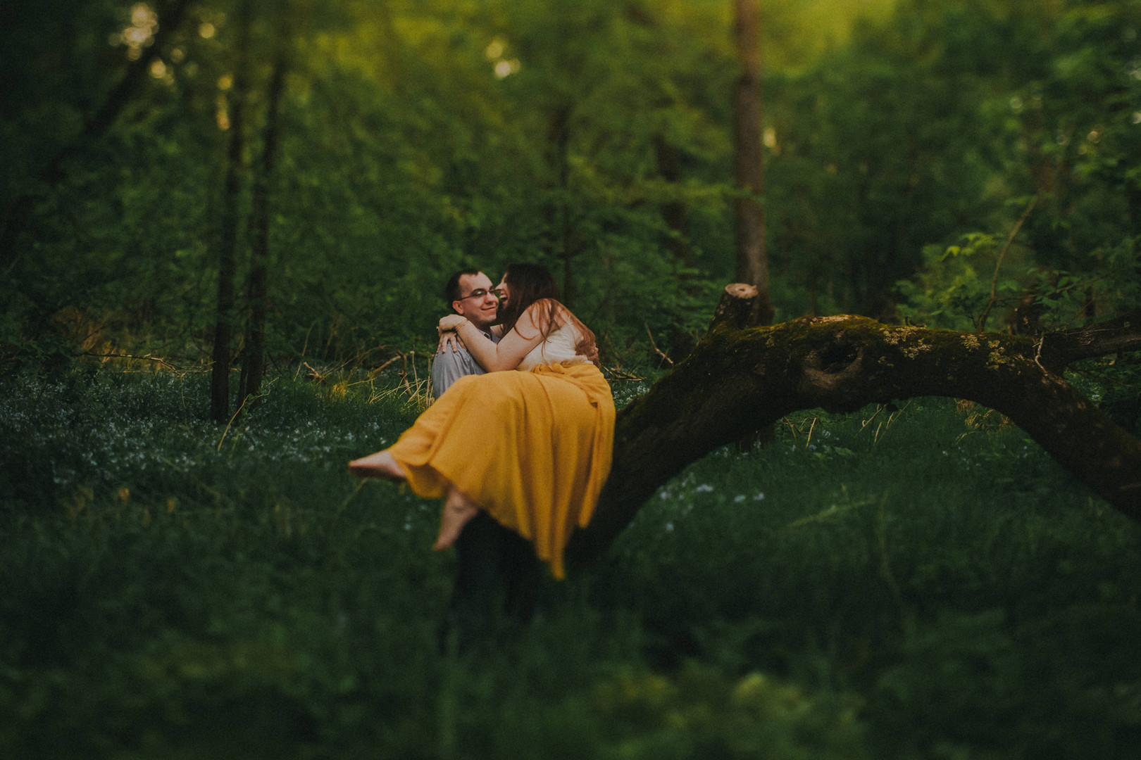 A man holds a woman in a forest during a Kickapoo, Wisconsin engagement session