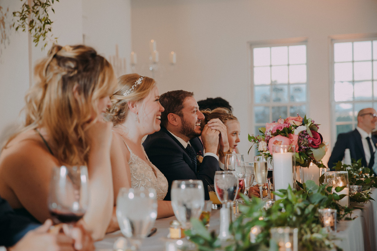 The wedding party seated at the head table smiles out at the crows during a Manor House wedding