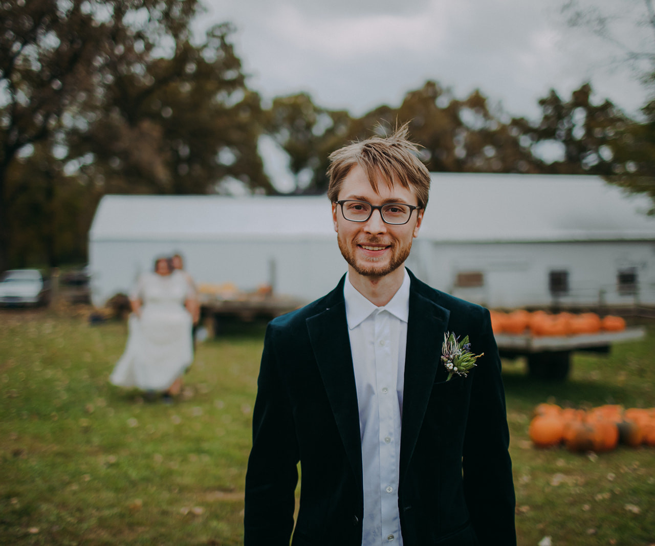 A groom smiles at the camera as he waits for his bride to approach - Wisconsin wedding photographer