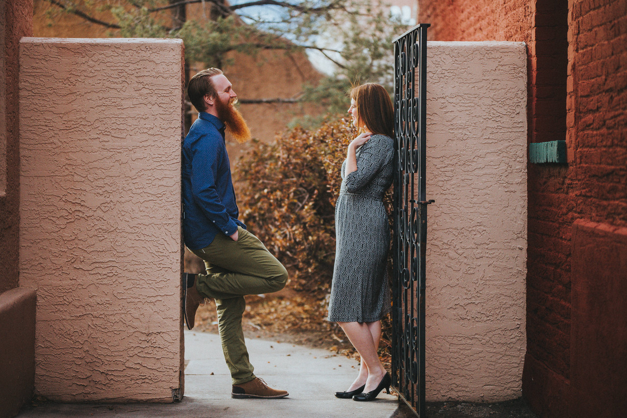 A man and woman lean against a open air door frame during at Downtown Colorado Springs, Colorado engagement session