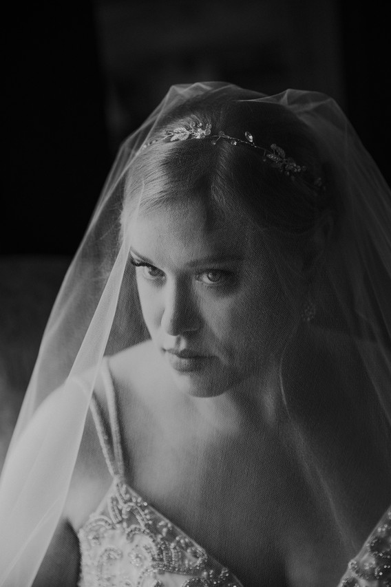 A close up of a bride with a veil over her face at The Manor House
