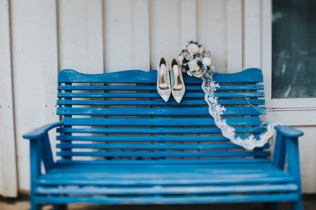 A pair of shoes, a veil, and a bridal bouquet rest on the back of a bright blue bench in Crested Butte Colorado