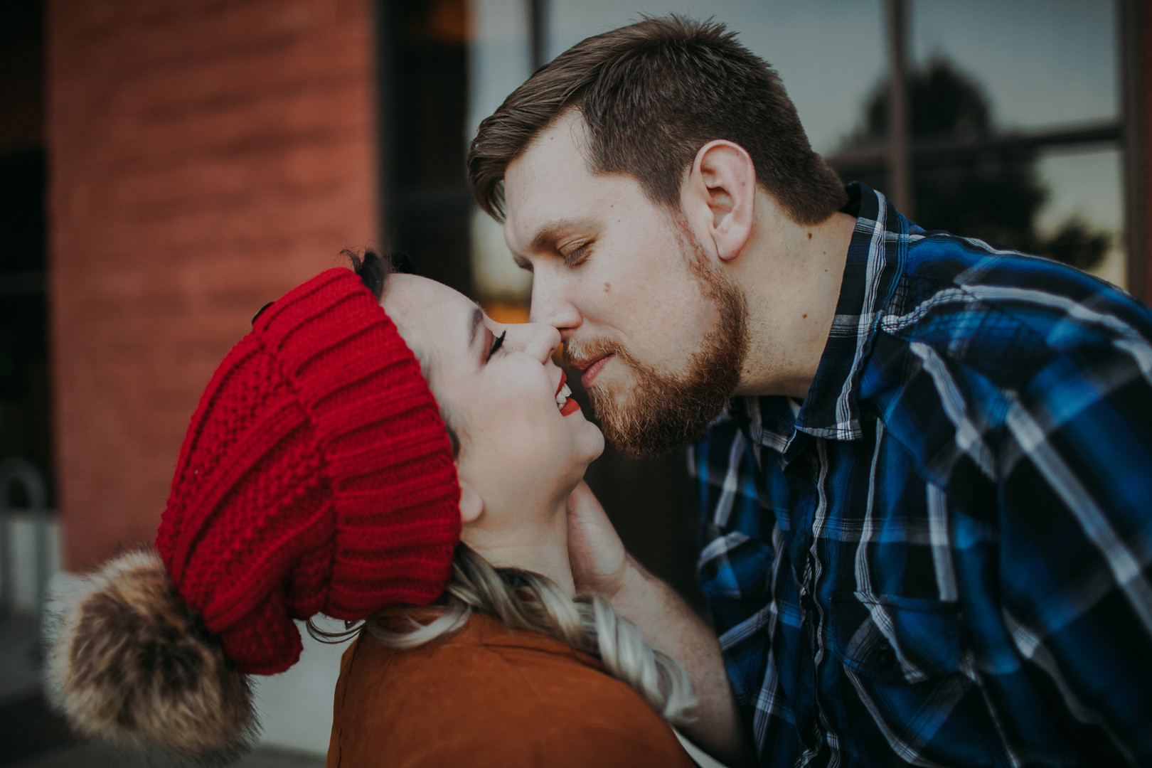 A close up of a man and woman kissing in front of O'so Brewing Company