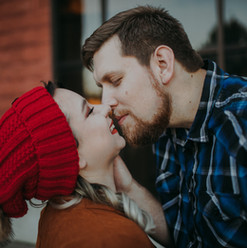 A man and woman embrace outside of O'so Brewing Co in a Central Wisconsin engagement session