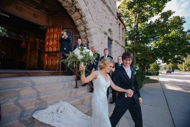 A bride and groom emerge from a downtown Oshkosh wedding ceremony