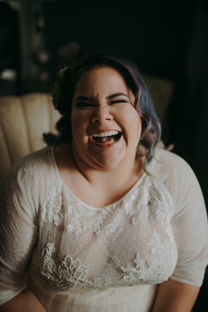A bride with blue hair laughs at the camera