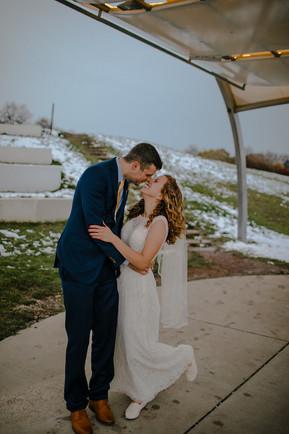A groom and bride kiss inside the Kadish Park amphitheater