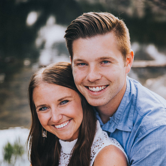 A close up of a man and woman smiling at the camera at a Dream Lake engagement session in Rocky Mountain National Park