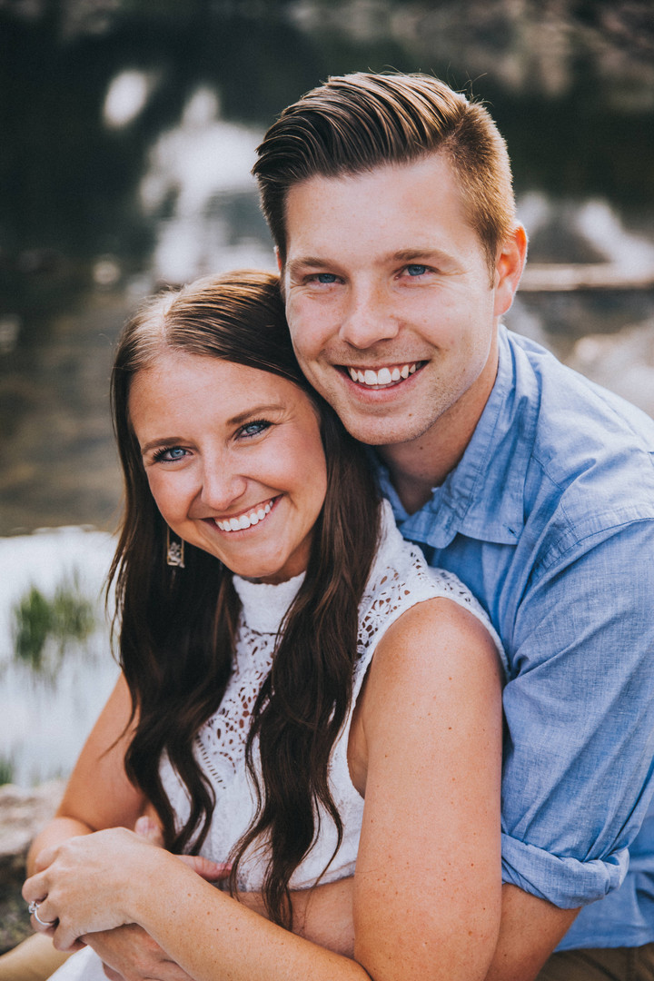 A close up of a woman and man smiling at the camera at a Dream Lake engagement session in Rocky Mountain National Park