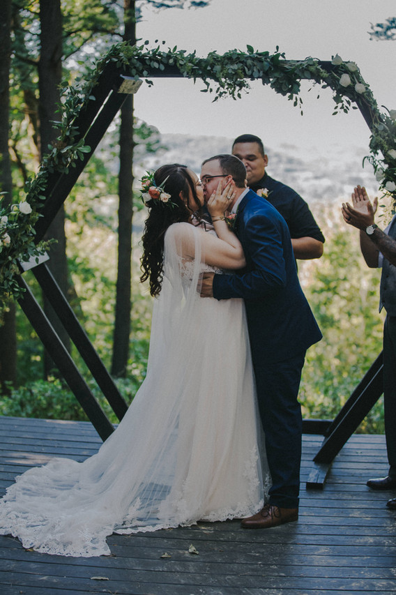 A bride and groom share their first kiss in front of an octagan arch during their wedding ceremony at Wildcat Mountain State Park