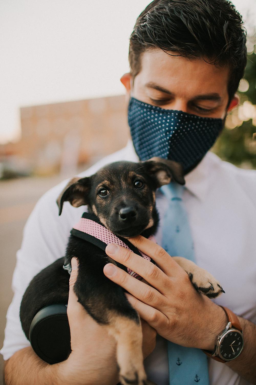 A man holds a puppy at a Baraboo Arts wedding