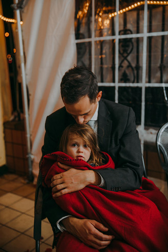 A little girl is snuggled by her dad