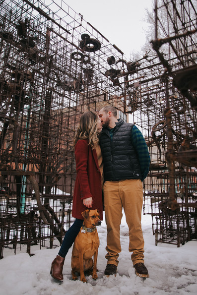 A man and woman kiss as they pose with their dog on Catalano Square Milwaukee