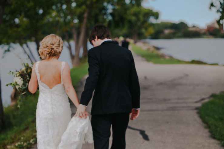 A bride and groom walk on a pathway