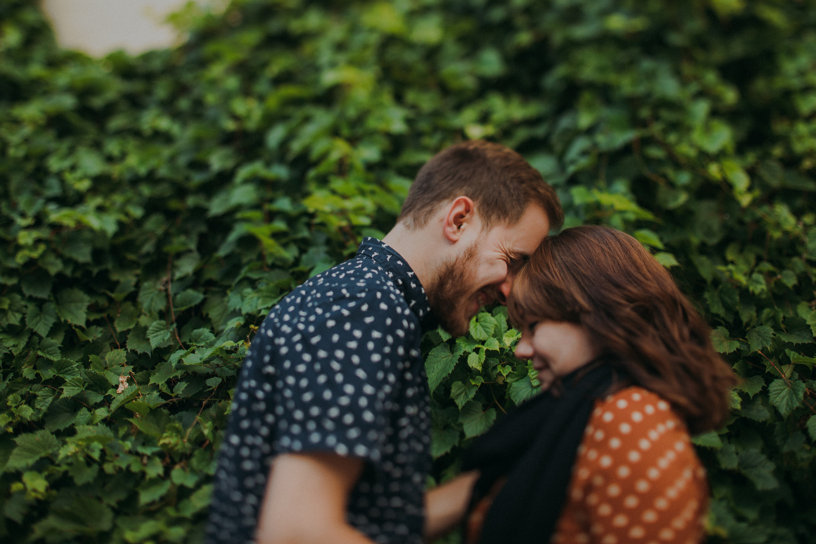 A man and woman touch foreheads in front of a wall of green ivy in a Downtown Stevens Point engagement