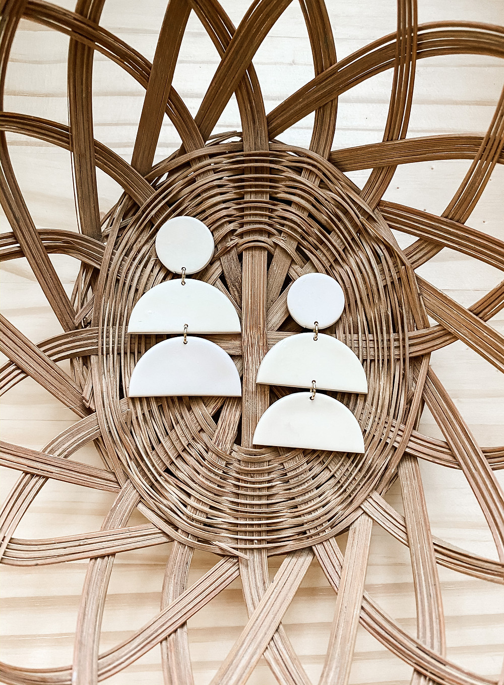 A pair of three-tiered earrings by Honeymoon Clay Co rests in a whicker basket in Winter Garden, FL
