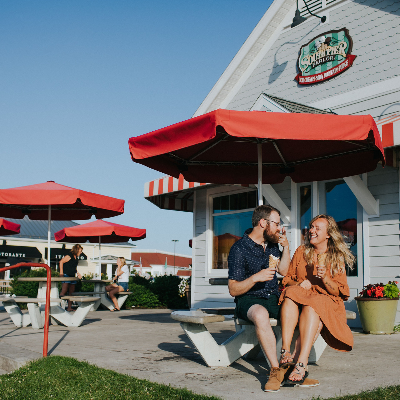A man and woman laugh together at South Pier Parlor - Sheboygan Engagement Photos