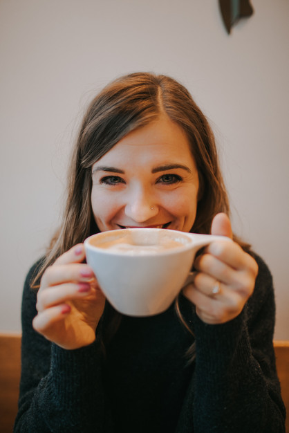 A close up of a woman smiling over a cup of coffee