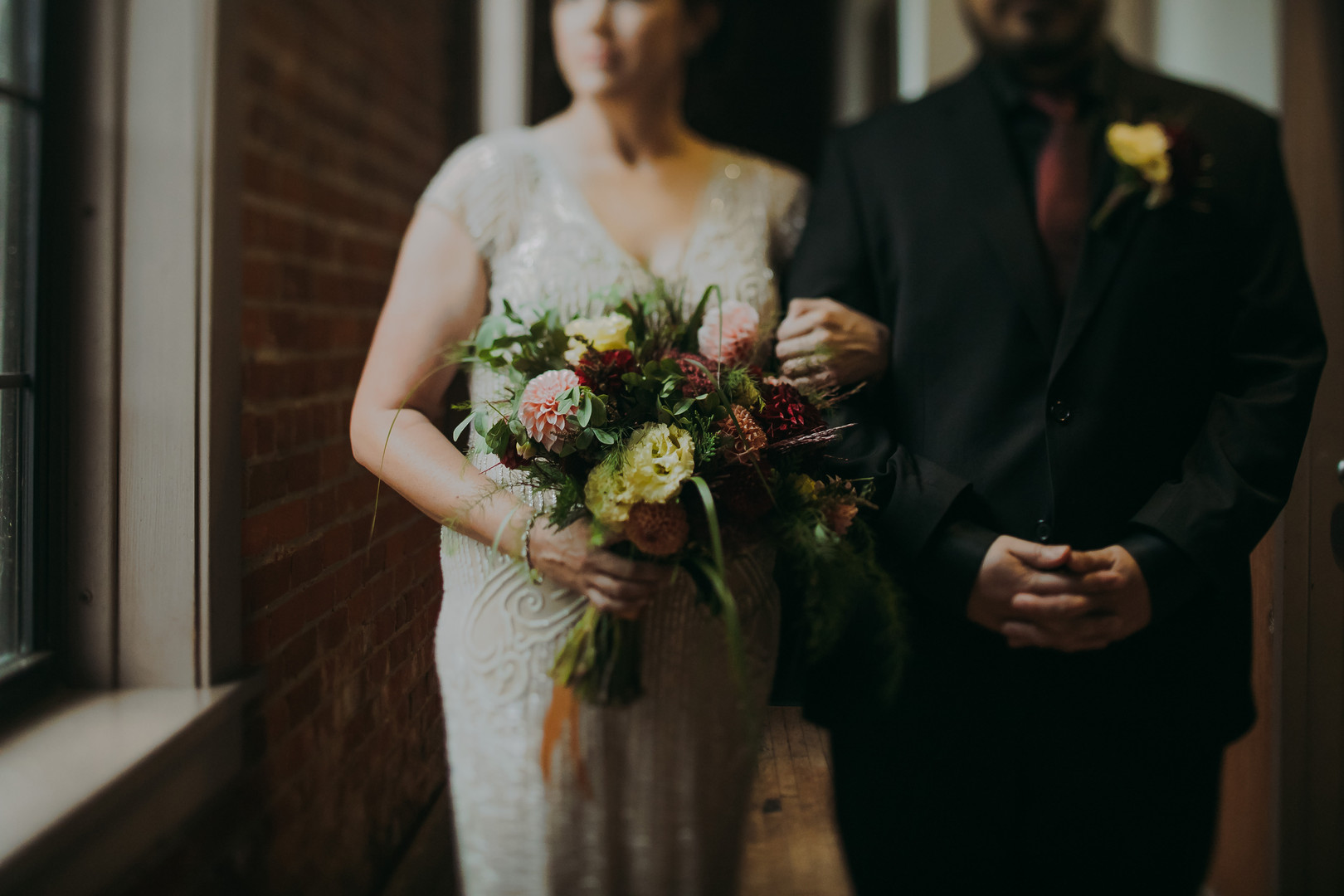 A close up of the bride holding her bouquet and a groom crossing his hands at The Pfiffner Building in Stevens Point Wisconsin