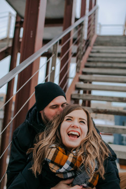 A man and woman laugh together on stairs in Kadish Park Milwaukee photos