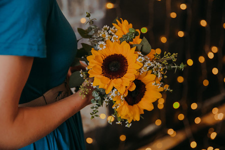 A close up of a bridesmaid holding a sunflower bouquet in Milwaukee, Wisconsin