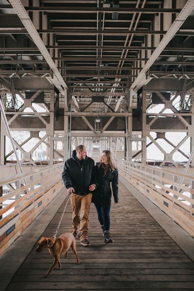 A man, woman, and dog walk across a bride during Kadish Park engagement photos