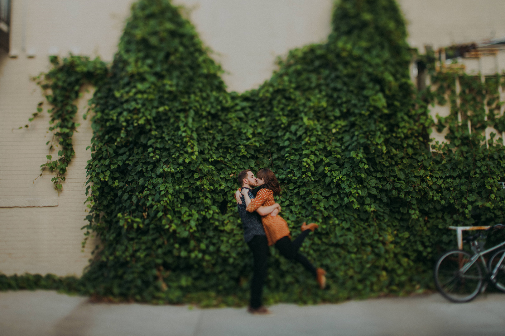 A man picks a woman up in front of a wall of ivy at a Downtown Stevens Point engagement session