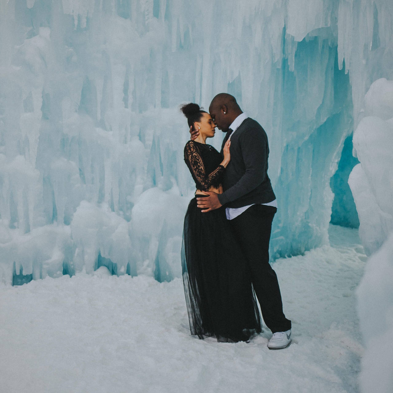 A man and woman lean in to each other in the Lake Geneva Ice Caves