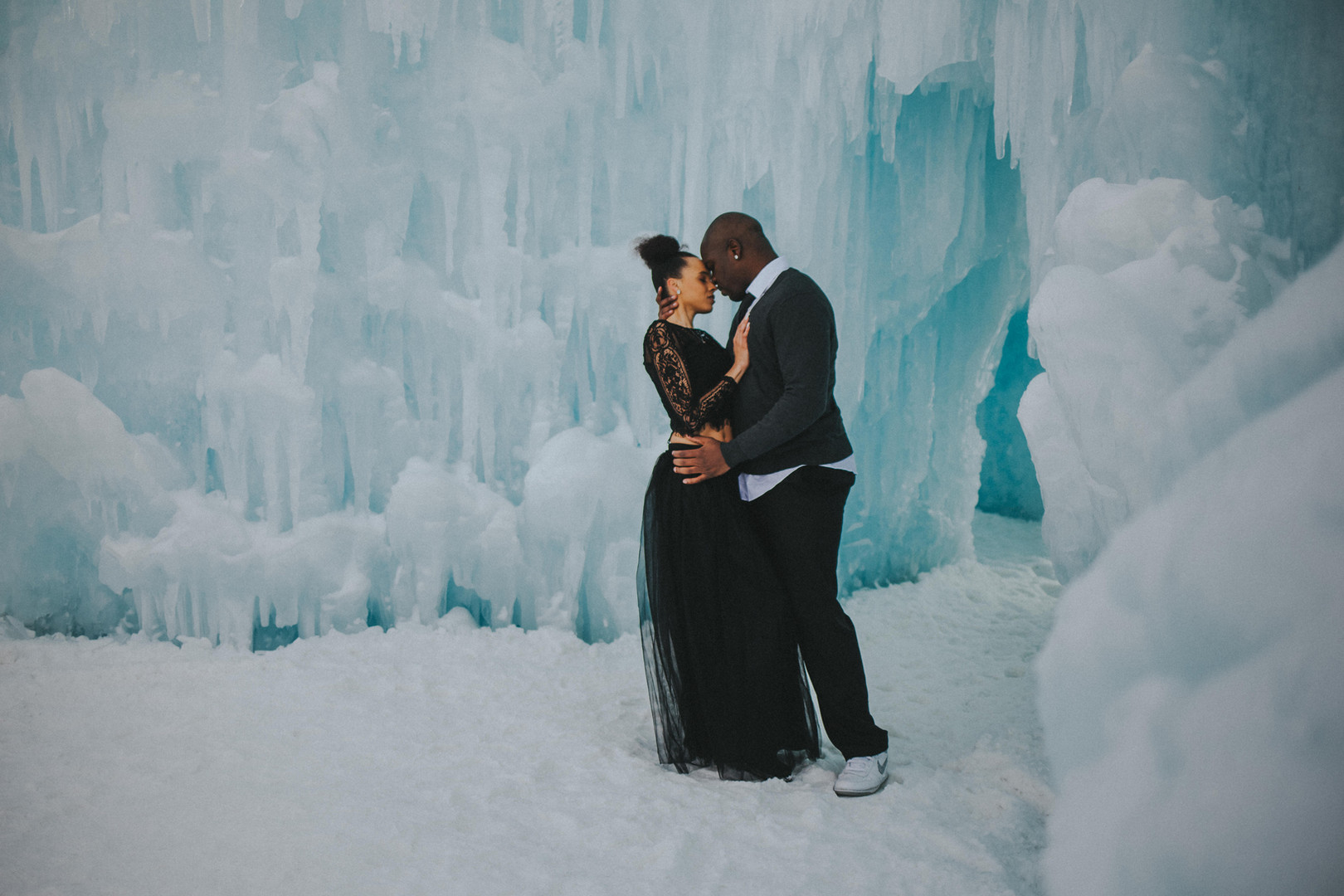 A woman and man touch forheads in the Ice Castles in Lake Geneva Wisconsin