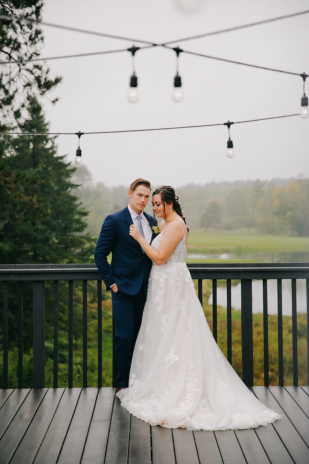 a bride and groom stand under edison light bulbs - Wisconsin Wedding Photographers